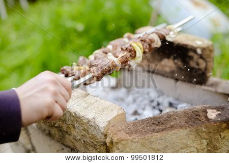 Man's hand holding stick of shashlik grilled over charcoal