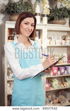 Beautiful young saleswoman is serving her customer