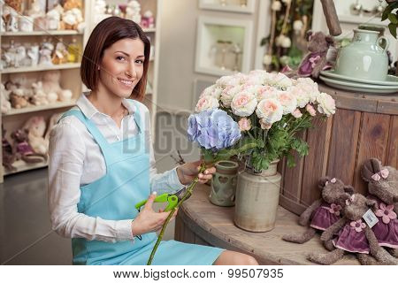 Cheerful young florist is working in her store