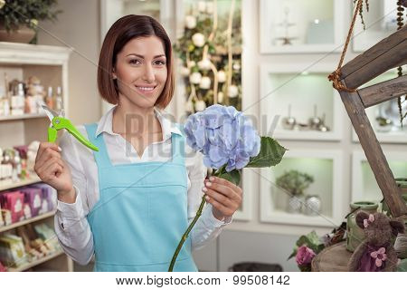 Beautiful young saleswoman is working in flower shop
