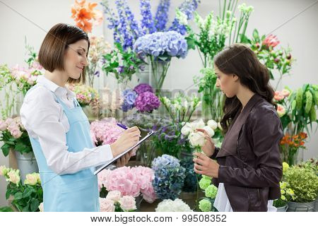 Skilled cheerful saleswoman is serving client in flower shop