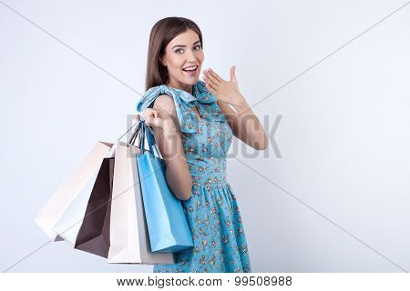 Cheerful young girl is purchasing a lot of clothing