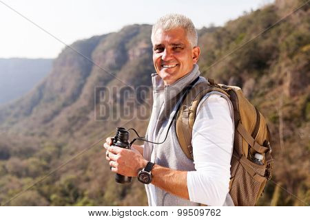 smiling mature man on top of the mountain