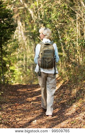 back view of senior female hiker walking in forest
