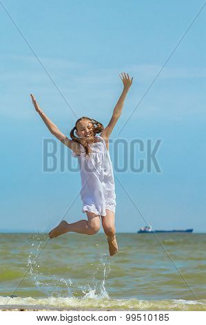 Happy Girl Jumping Over The Sea