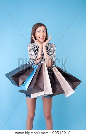 Cheerful young girl is crazy about shopping