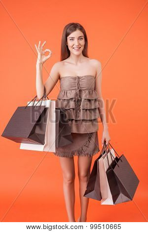 Beautiful girl with packages is expressing positive emotions