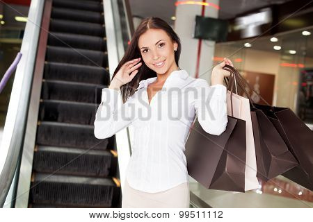 Cheerful young woman is buying clothing in boutique