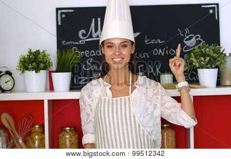 Chef woman portrait with  uniform in the kitchen and pointing up