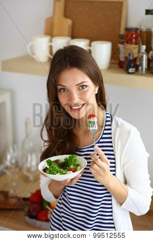 Young woman eating salad and holding a mixed salad