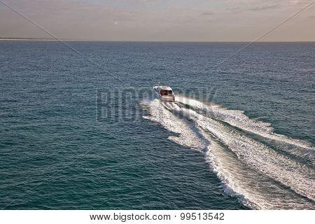 Small Boat Sailing Through A Calm Sea