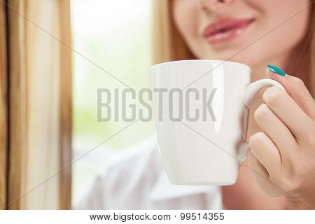 Cheerful young girl is drinking hot coffee