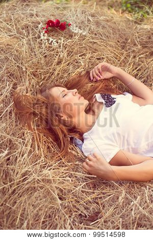 Sensual blonde young girl in white dress sleeping on hay