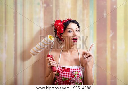 Funny joyful beautiful pinup lady with paint roller