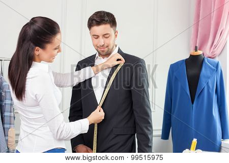 Attractive young female tailor is working with a client