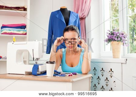Attractive young female tailor is working hard