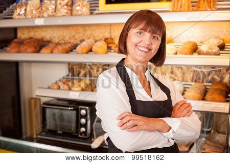 Cheerful female baker is presenting her pastry