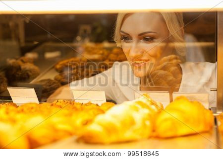 Attractive young woman is ready to buy sweet pastry