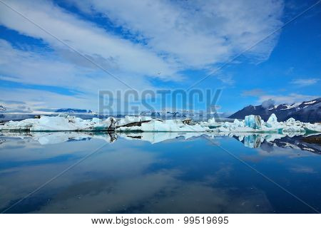 Blue and turquoise icebergs and cirrus clouds are reflected in the Bay Yokulsarlon in Iceland. Sunrise. Reflection.