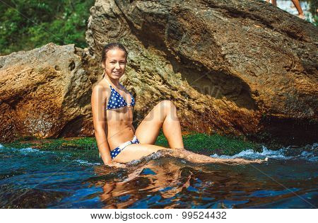 girl relaxing on stones of in the sea