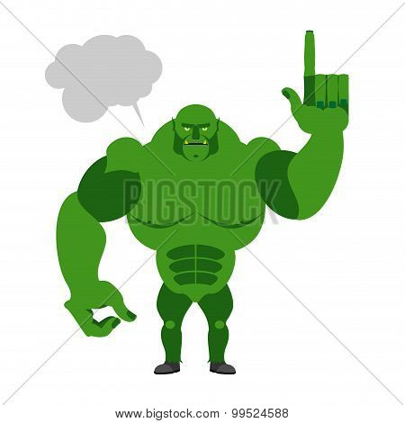 Green Goblin With A Text Bubble. Finger Shows Up. Big And Powerful Monster On A White Background