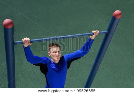Shot of strong athlete man doing pull-up on horizontal bar over the grass background