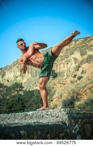 man the athlete trains karate on a beach