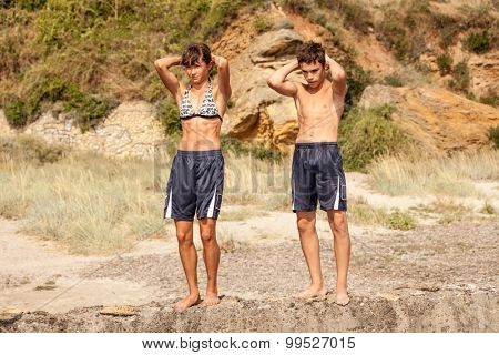 Teen Athletes stands on a rock