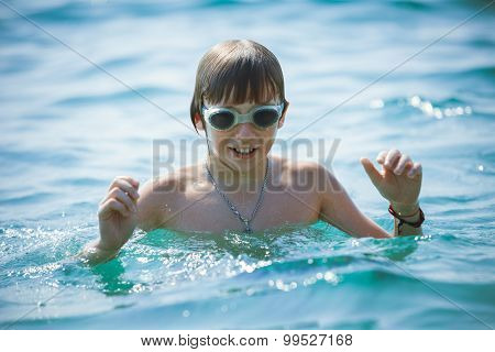 Portrait of playful boy in swimming goggles on sea