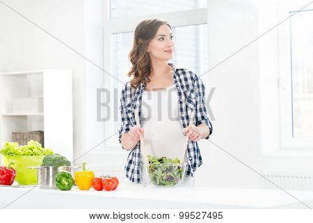 Beautiful pregnant woman mixing salad with wooden spoons.