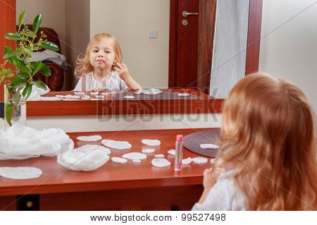 Pretty little girl with cosmetics near dressing table in the room