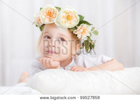 happy little girl with a wreath on the head on a bed