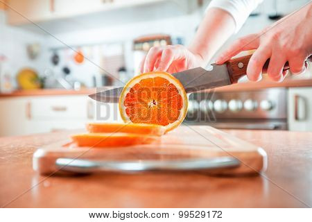 Woman's hands cutting fresh orange on kitchen