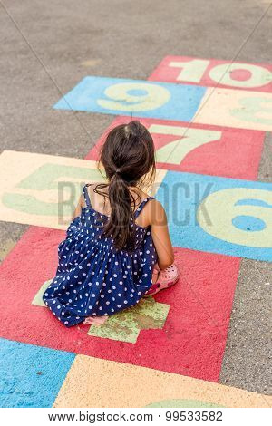 Little Girl Playing Hopscotch / Little Girl Playing Hopscotch On Playground