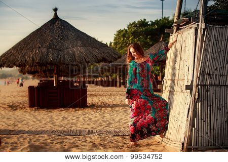 Slim Girl In Long And Big Red Hat Leans On Reed Wall On Beach