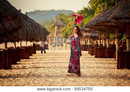 Slim Girl In Long Waves Big Red Hat Among Reed Umbrellas