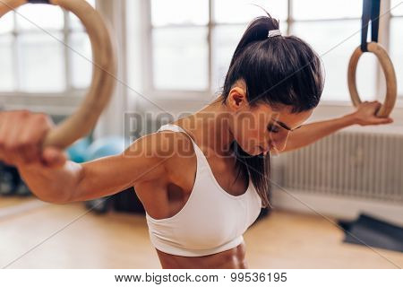Fit Young Woman Exercising With Gymnast Rings