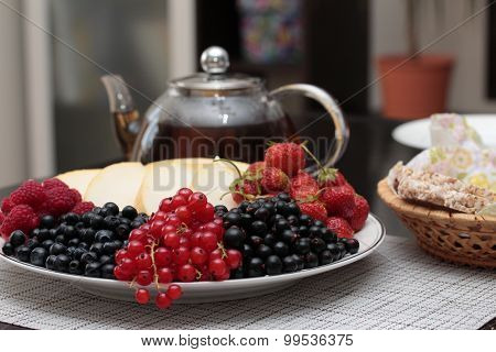 A plate of fruits and red currants on the foreground