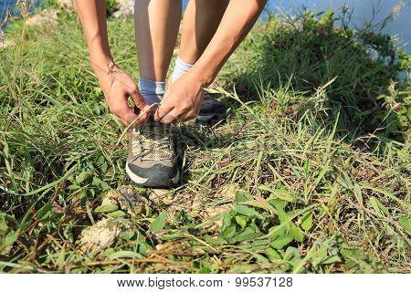 woman hands tying shoelace on seaside mountian grass
