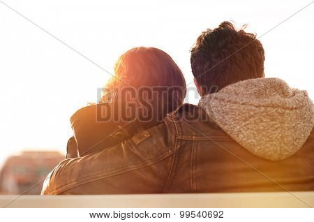 Closeup rear view of man embracing his woman while sitting on bench. They are sitting outdoor and looking away in a beautiful sunset light. Contemplative and aspirational mood.