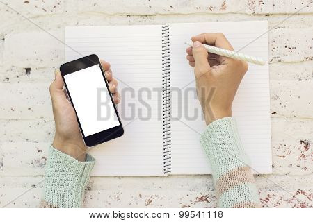 Girl Writes In A Diary With Blank Cell Phone, Mock Up