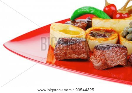 european food: roast beef meat goulash over red plate isolated on white background with tomatoes and dill and bbq sauce