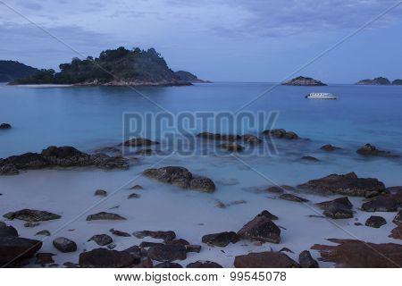 Long exposure view of sea against rocks at dusk