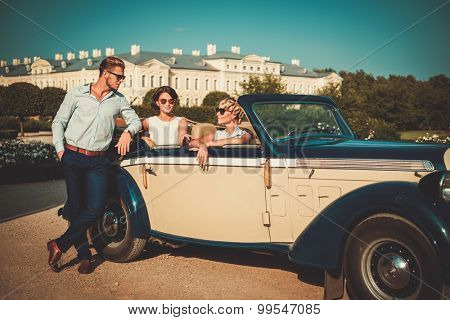 Wealthy friends in a classic convertible near royal palace