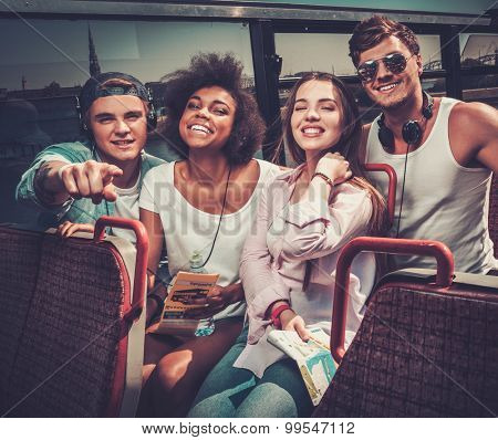 Multinational friends riding on a sightseeing bus