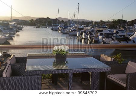 Table With Chairs In Front Of A Marina