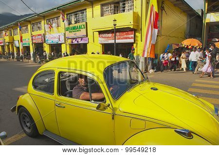 People in a vintage car pass by the street of Kandy, Sri Lanka.