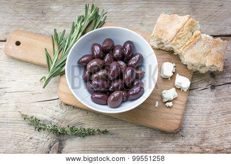Kalamata Black Olives, Bread, Feta Cheese And Herbs On Rustic Wood