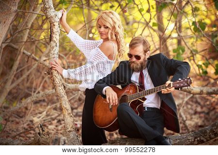 Bearded Guitarist And Girl Sit On Tree Branch