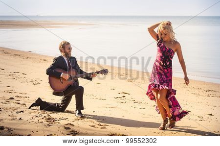 Blonde Girl And Guitarist On Beach At Low Tide